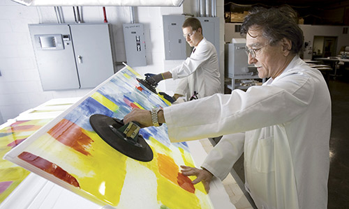 Bullseye Glass founder Dan Schwoerer examines some panels to be used in a large-scale work